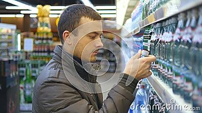 Bottiglia di scelta e d'acquisto del giovane di acqua minerale al supermercato Tipo che prende prodotto dagli scaffali alla drogh stock footage