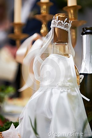 Bottle of champagne in costumes of bride