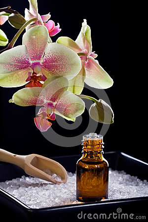 Bottle of essential oil with orchid flowers