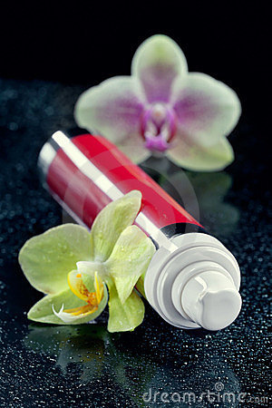 Bottle of face cream/lotion with orchid flowers