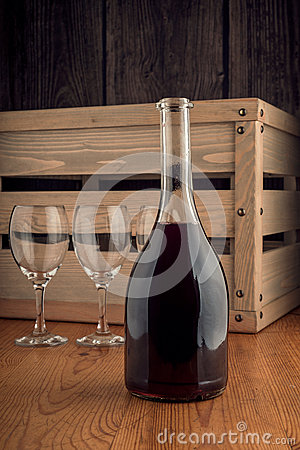 Bottle and a glass of wine on a wooden backgroung