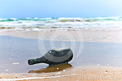 Bottle with a note on the sea shore