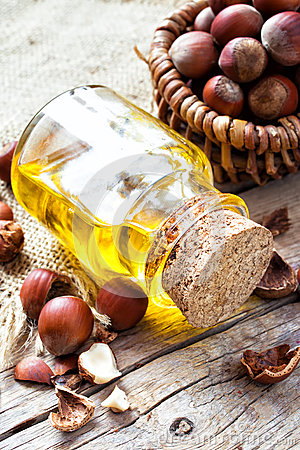 Free Bottle Of  Healthy Nut Oil And Basket With Hazelnuts On Table Royalty Free Stock Image - 49022986
