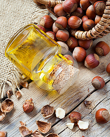 Free Bottle Of Nut Oil And Basket With Hazelnuts On Old Kitchen Table Royalty Free Stock Photos - 47212678