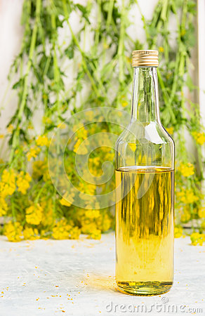 Free Bottle Of Rapeseed Oil On White Wooden Table Over Fresh Rape Flowers Royalty Free Stock Images - 56261229