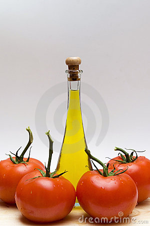 Bottle of oil and four tomatoes