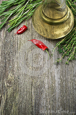 Bottle of olive oil and herbs on a wooden background
