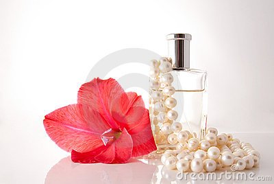 Bottle with perfume, a pearl necklace a flower