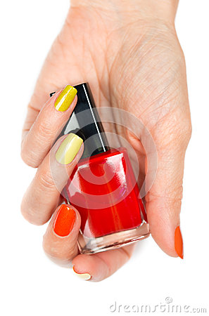 A bottle of red nail polish in a female hand