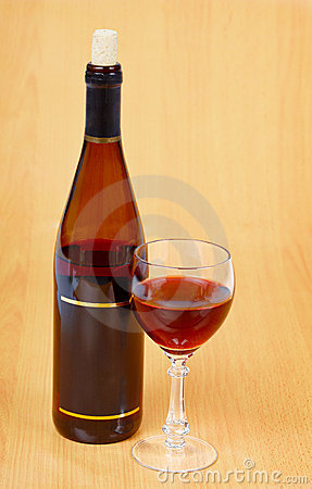 Bottle of red wine and glass on wooden table