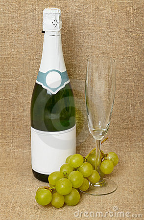 Bottle of sparkling wine, glass and grapes
