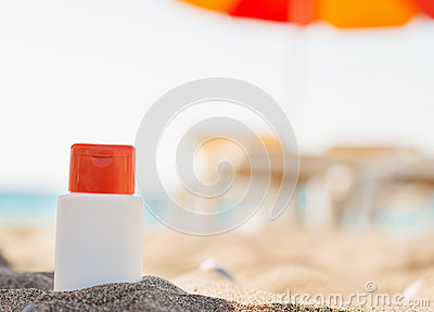 Bottle of sun block creme in shadow on beach