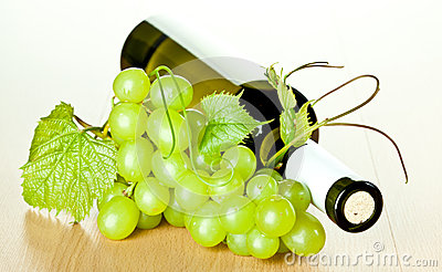 Bottle of white wine and green grapes