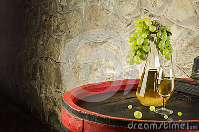 Bottle of white wine, wine glass and white grapes on barrel