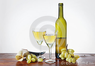 Bottle of wine and grape bunches on wooden table