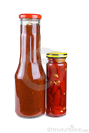 Bottles with tomato ketchup and chili peppers