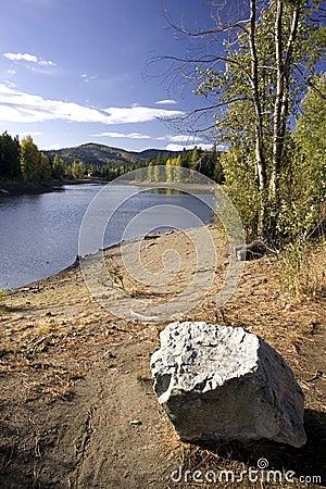 A boulder by a lake.
