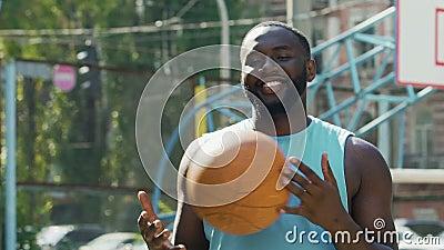 Boule de lancement d'homme heureux d'une main à l'autre, fier de la victoire de streetball banque de vidéos