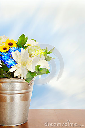 Bouquet of bright flowers in a metal bucket on wooden surface