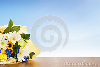 Bouquet of flowers on a wooden surface against blue sky