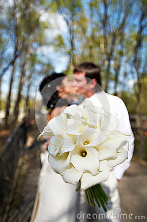 Bouquet kala against romantic kiss bride and groom