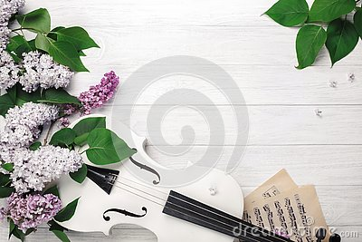 A bouquet of lilacs with violin and music sheet on a white wooden table. Top wiev with space for your text Stock Photo