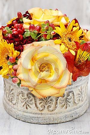 Bouquet of orange roses and autumn plants in vintage ceramic vas