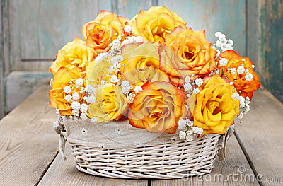 Bouquet of orange roses in a white wicker basket