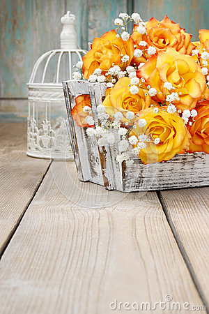 Bouquet of orange roses in a white wicker basket and vintage bir