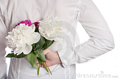 Bouquet of peonies behind the back of the man