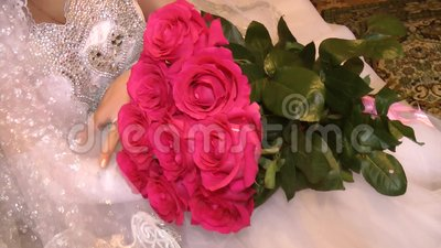 Bouquet of red roses on the lap of the bride stock video footage