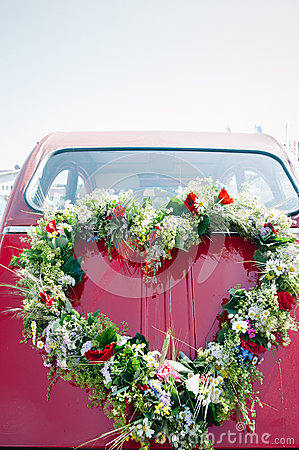 Bouquet on a red wedding car