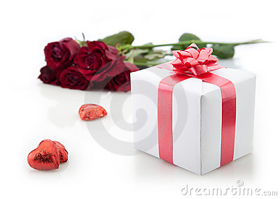 A bouquet of roses and gift on white background.