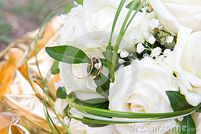 Bouquet of white roses with closeup of golden wedding rings on white rose