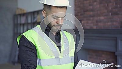 Bouwer in de helm en het groene jasje die tekeningen onderzoeken Beroeps op het werk Man die door papieren kijkt stock footage