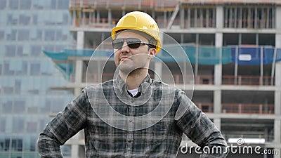 Bouwer kaukasus in een helm en zonnebril tegen de achtergrond van een bouwlocatie op een zonnige zomerdag stock footage