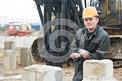 Bouwer in vuile workwear bij bouwwerf