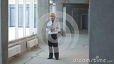 Bouwingenieur, zakenman, makelaar in onroerend goed binnen een nieuwe de bouw het inspecteren bouwwerf die tablet gebruiken stock footage