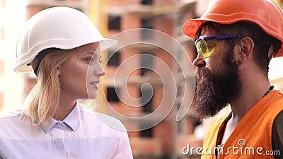 Bouwvakker en ingenieur die bij bouwwerfplaats spreken Arbeiders in helmen bij de bouw van gebied Mannetje en Wijfje stock video