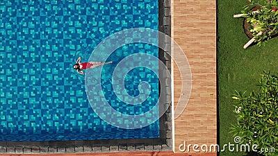 Bovenaanzicht van slanke jonge vrouw in rood bikini, zwevend in kristalhelder water dat op de rug zwemt en geniet van zwemwater stock footage