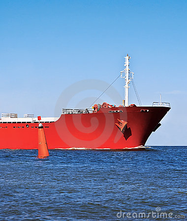Bow of the red ship in the ocean and a red buoy.