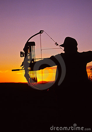 Bowhunter at Full Draw in Sunset