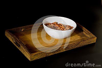 Bowl with almonds on wooden tray