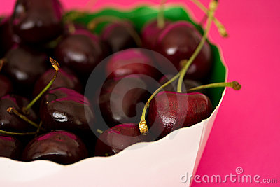 Bowl of black cherries on bright pink background