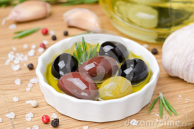 Bowl with different olives in olive oil and spices on wood