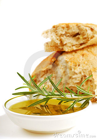 Bowl of olive oil with crusty bread and rosemary