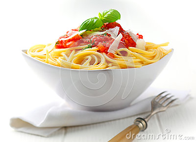 Pasta in a white bowl with tomato sauce and fresh basil set against a ...