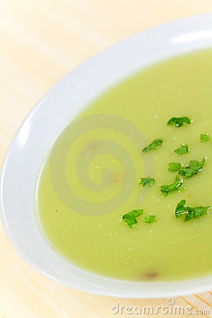Bowl of pea soup garnished with  cream and crouton