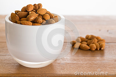 Bowl of raw almond nuts on wooden table