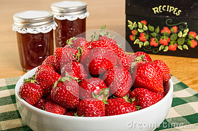Bowl of strawberries and jars of jam